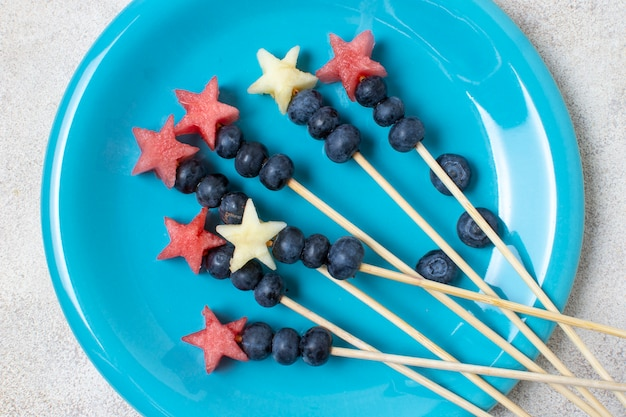 Flat lay independence day fruit skewers on plate