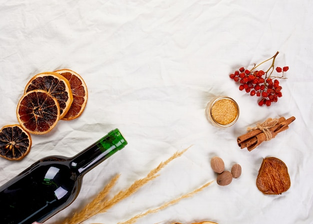 Flat lay of ingredients and bottle of red wine for winter seasonal mulled wine, christmas drink
