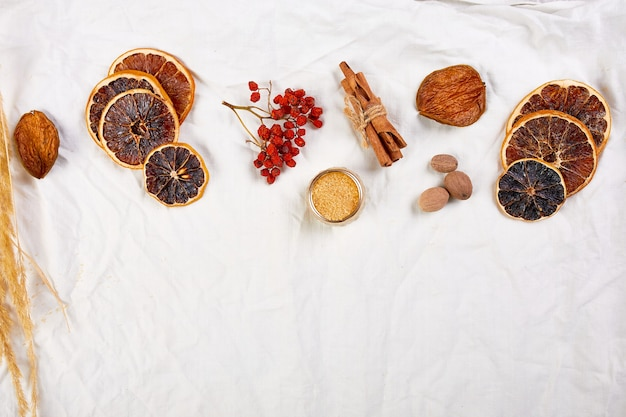 Flat lay of ingredients and bottle of red wine for winter seasonal mulled wine on white textile linen tablecloth, still life, cloth texture background, christmas drink, copy space.