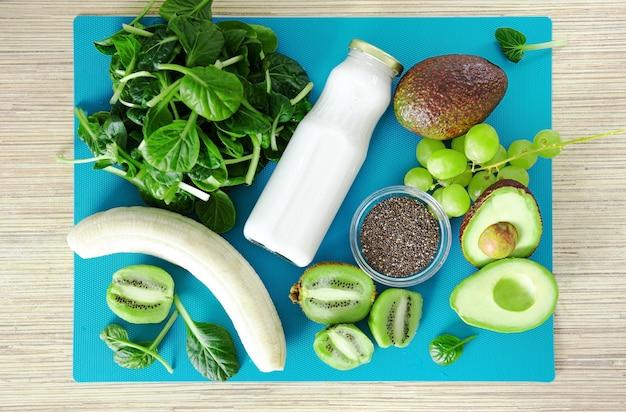 Плоские ингредиенты для зеленого смузи. вид сверху на бирюзовом фоне банана, шпината, семян чиа, кокосового молока в стеклянной банке, авокадо, винограда. детокс, рецепт смузи для здорового питания.