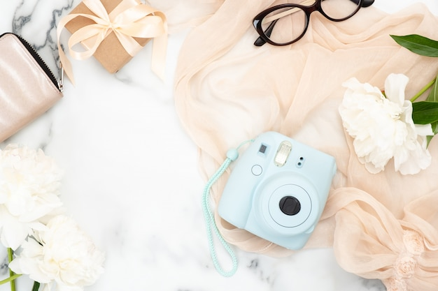 Flat lay instant film camera, glasses, purse, pastel pink woman scarf, white peony flowers