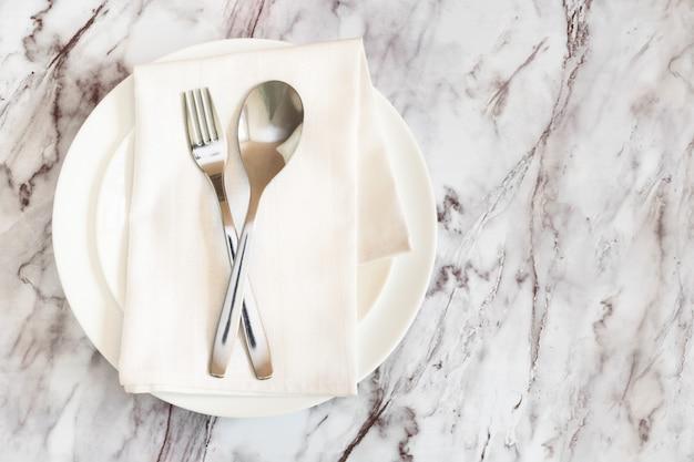 Плоский лежал столовые приборы, вилка и нож на салфетке на пустой белой тарелке на мраморном столе.