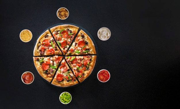 Flat lay of italian pizza and fresh ingredients around on dark surface top view