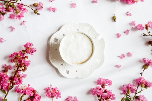 Flat lay items: coffee mug and pink flowers on white table