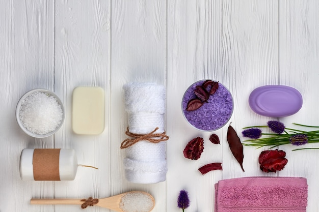 Flat lay items for spa treatment on white wooden desk