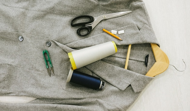 Flat lay. on the jacket lie scissors, a pencil, color spools, chalk, scissors for yarn, a hanger.