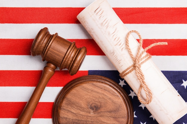 Flat lay judge gavel and the usa flag. top view old scroll with bow knot.