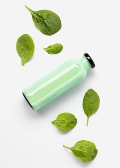 Flat lay of juice bottle with spinach leaves