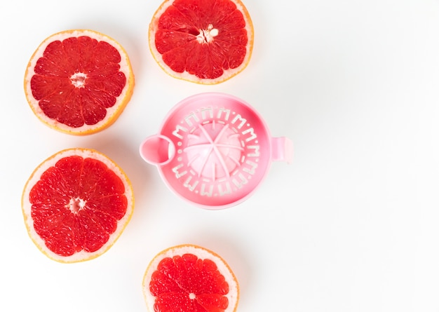 Flat lay juicer and grapefruit in halves