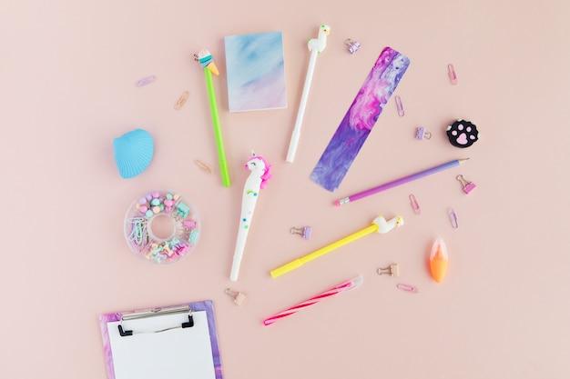 Flat lay of kawaii stylish school stationery on pink.