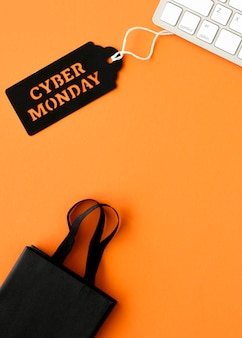 Flat lay of keyboard with cyber monday tag and shopping bag