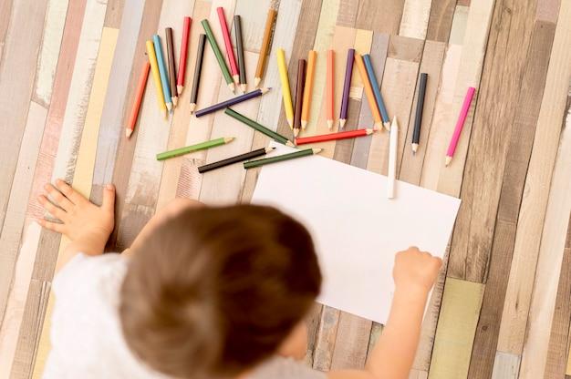 Flat lay kid on floor drawing