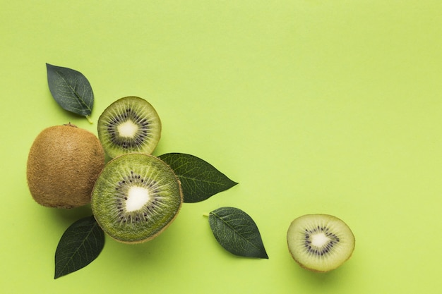 Flat lay of kiwi and leaves with copy space