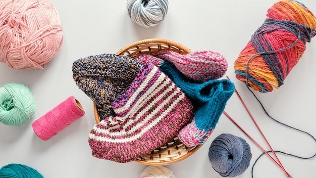 Ferri da maglia piatti laici e lana nel cesto