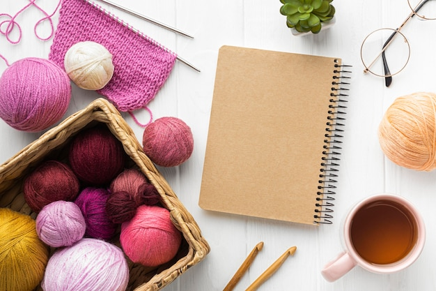 Flat lay of knitting set with basket and yarn