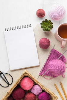 Flat lay of knitting set with notebook and yarn