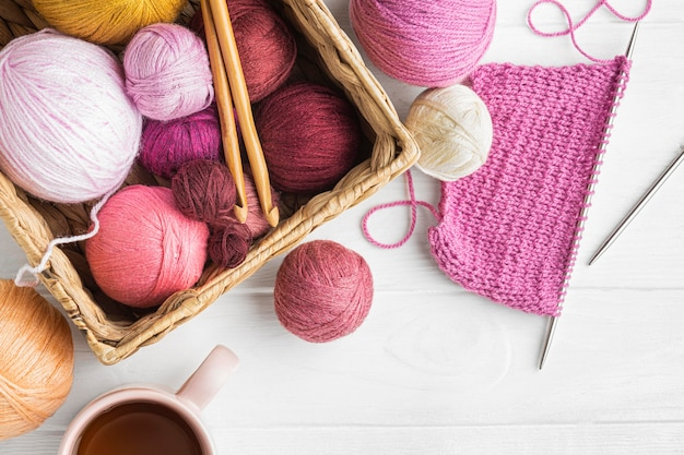 Flat lay of knitting set with yarn and basket