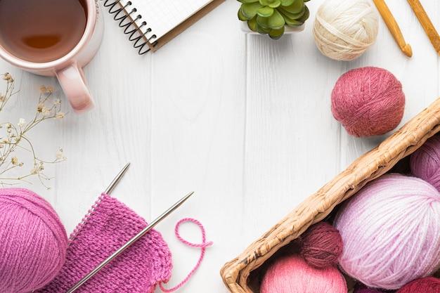 Flat lay of knitting set with yarn and tea