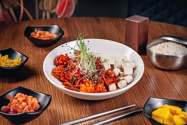 Flat lay korean traditional food with kimchi on wooden background. korean noodles with onions, red sauce and sesame, chicken meat. traditional asian cuisine. lunch. healthy food