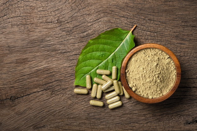 Flat lay of kratom (mitragyna speciosa) capsules with powder and fresh leaf on wood background.
