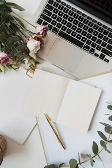 白紙のノート、ラップトップ、バラの花の花束、白いテーブルの上のユーカリの枝とフラットレイレディボスホームオフィスワークスペース