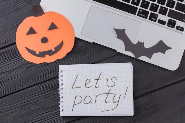 Плоский лежал ноутбук и хэллоуин аксессуары. блокнот со словами давайте вечеринку на темном деревянном столе.