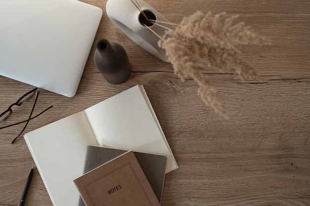 Flat lay of laptop, notebook, glasses on wooden