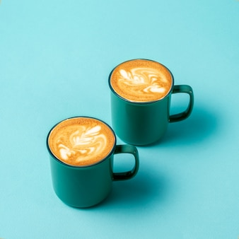 Flat lay latte art coffee in green cups on green background., copy space for text,top view.