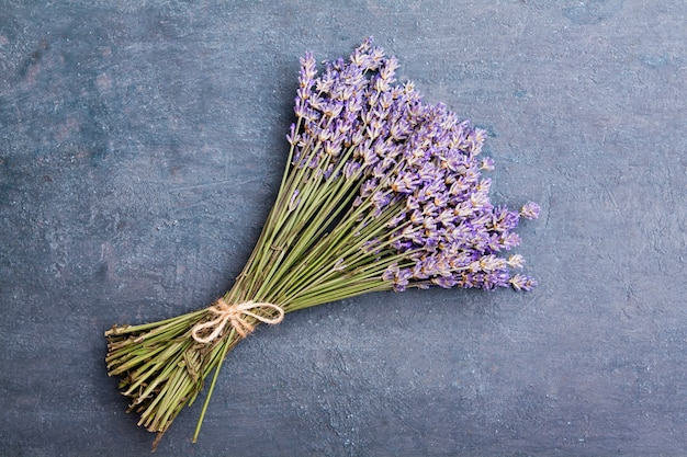 Flat lay lavender flowers in a bun on a dark textured background