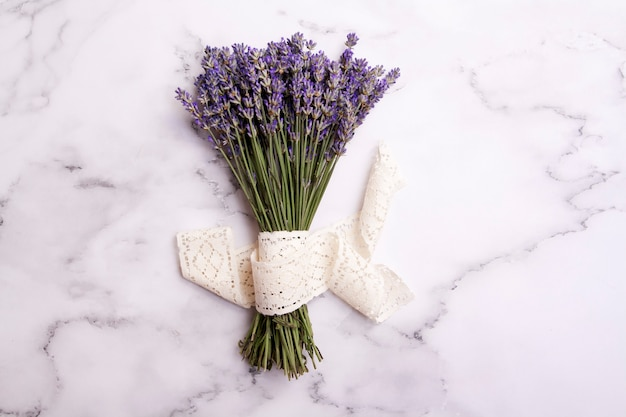 Flat lay lavender flowers in a bunch with lace on a marble table