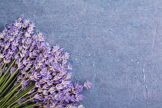 Плоские лежал цветы лаванды в булочке на темном текстурированном фоне с копией пространства