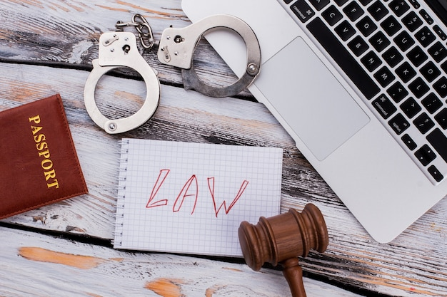 Flat lay law and punishment concept. handcuffs with judge hammer and laptop on white wooden table.