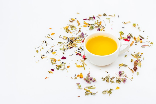 Flat lay layout of cup of green tea with assortment of different dry tea leaf and ginger on white background, copy space for text