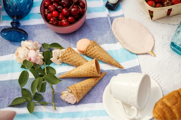 Flat lay layout with cherries waffle cones and flowers.