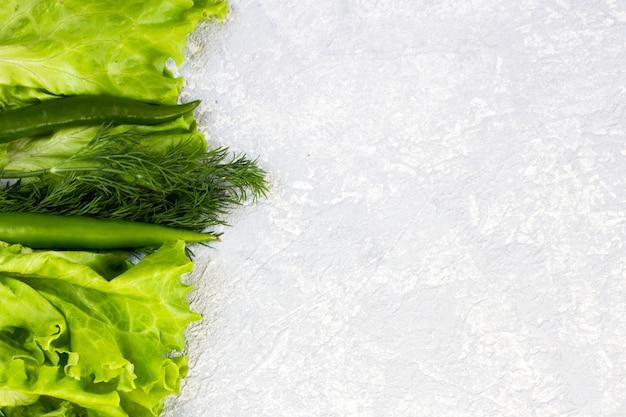 회색 배경에 수분이 많은 채소가있는 평평한 레이아웃. 텍스트를위한 공간을 복사하십시오. 적절한 영양과 건강한 식습관의 개념입니다. 유기농 및 채식 음식.