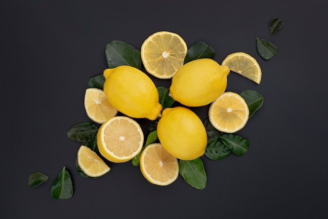 Flat lay of lemons and slices with leaves