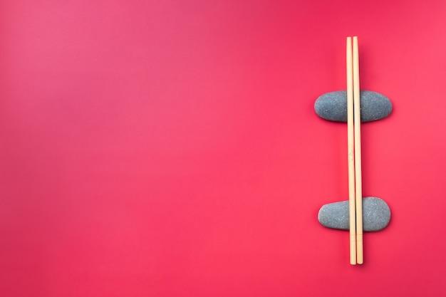 フラットレイ。ピンクの背景の楕円形の石の上に軽い木の箸があります。伝統的なアジアのカトラリー。コピースペース