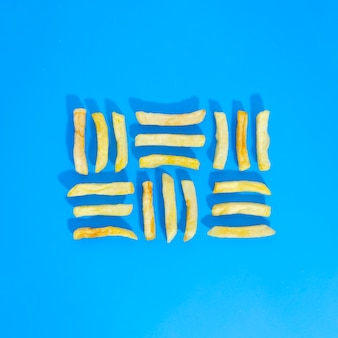 Flat lay of lined fries on blue background