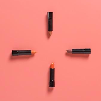 Flat lay of lipsticks on plain bakground