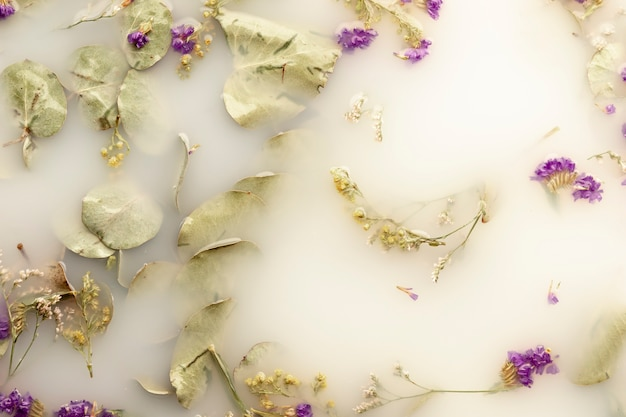 Flat lay little purple flowers in white colored water