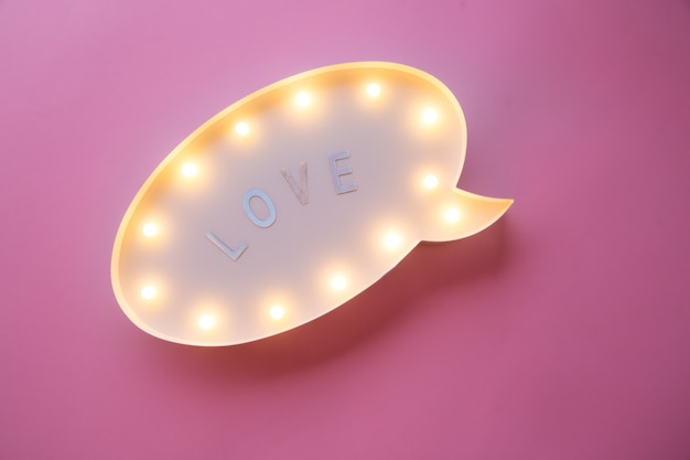 Flat lay love holiday celebration text i love you on lightbox on pink