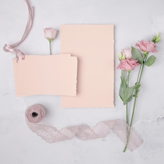 Flat lay lovely arrangement with wedding invitations and flowers