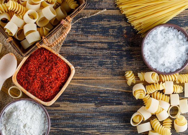 Flat lay macaroni pasta with salt, red spice, spaghetti on wooden background. horizontal space for text