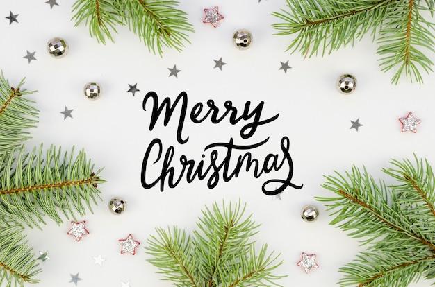 メリークリスマスのテキストのレタリングとクリスマスの装飾が施された枝で作られたフラットレイ