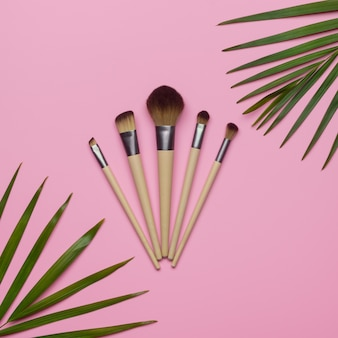 Flat lay of make up brush sets arranged with green palm leaves on pink background