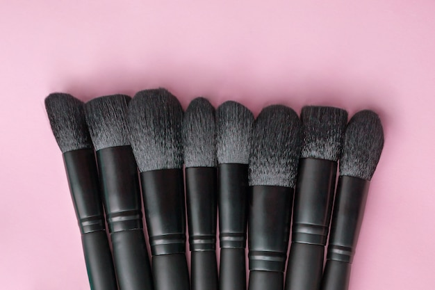 Flat lay of makeup brushes collection on colorful space.