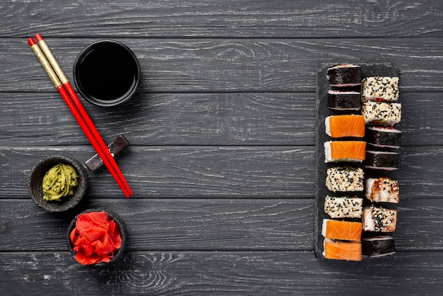 Flat lay maki sushi assortment on slate with chopsticks