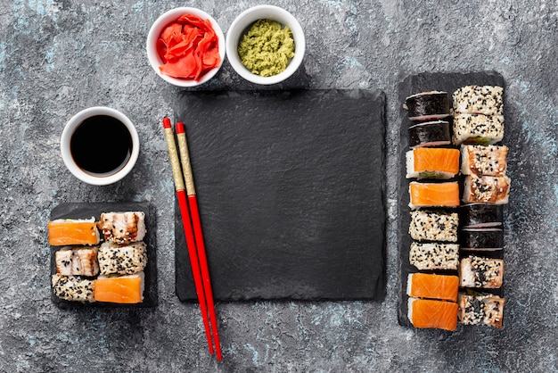 Flat lay maki sushi rolls chopsticks and soy sauce with blank slate