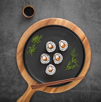 Flat lay maki sushi rolls with chopsticks and soy sauce
