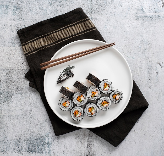 Flat lay maki sushi rolls with chopsticks